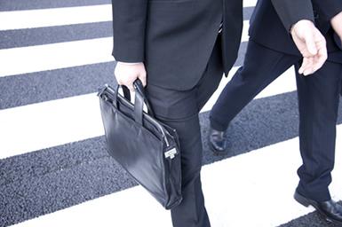 横断歩道の上を歩くビジネスマン達